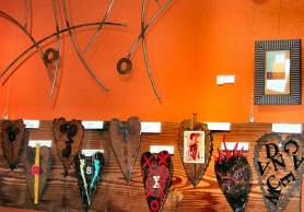 by: Elizabeth Ussher Groff, Some of Jill Torberson's welded metal hearts are on display at First Cup Coffeehouse in Woodstock, in time for Valentine's Day.