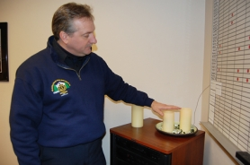 "by: Anthony Roberts, CCFD #1 firefighter Steve McAdoo demonstrates how the ""flameless"" candles turn on and off."