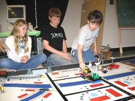 by: Ray Pitz, ROBOT CROSSING – From left to right, Avery Pierce, Josh White and Brett Stoddard, all members of the Lego robotics team, run their robots through their paces while practicing for state competition at Archer Glen Elementary School.