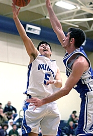 by: MILES VANCE, CHALLENGING — Valley Catholic junior Kent Kassel launches a shot attempt over Amity's Steven Wolfe during his team's Friday home loss.
