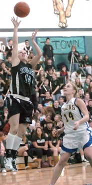 by: DAN BROOD, DRIVING — Tigard junior Melissa Woolard (left) goes up to the basket right before the end of the third quarter in the win over Newberg.