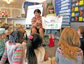 by: JIM CLARK, In a pre-kindergarten class at Southwest Charter School, Clara Michel, 5, displays her drawing in show and tell, with teacher Mary Esterline offering encouragement. Charter schools seem to attract as many detractors as they do proponents.