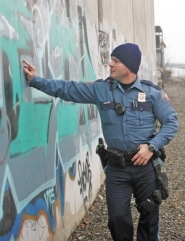 by: KATIE HARTLEY, Portland police officer Matt Miller, the bureau's graffiti investigator, looks at tags on the walls of a Portland warehouse. For some readers, new restrictions go too far, while for others, they don't go far enough