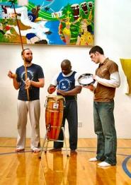 "by: Merry MacKinnon, Patrick Kreipe, Mestre Almiro Aguilino dos Santos, and Ben Hamlin here practice playing the traditional Brazilian music that accompanies ""capoeira"" – a martial art originally created by slaves who disguised the forbidden activity as a dance."
