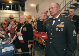 by: Vern Uyetake, Staff Sgt. Daniel Dagett, right,  whose 41st  unit  out of LaGrande is soon to be deployed, salutes the flag while the national anthem is played. Honored guest Col. Ken Reusser, left and his wife Trudy stand at attention.