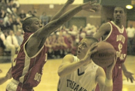 by: David Ball, Wilson's Gage Aker looks for an opening on the baseline, while David Douglas defender Andre Eddings leaps out to block his path. The Trojans won Wednesday's playoff game 67-51.