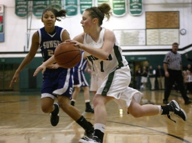 by: JAIME VALDEZ, DRIVING TIGER — Tigard junior Corinn Waltrip (right) looks to drive to the basket against Sunset's Alyssa Martin in last week's state playoff game. Sunset came away with a 31-28 victory.