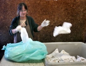 by: JIM CLARK, A gloved Cindy Martin counts incoming diapers at Tidee Didee's Southeast Portland facility.
