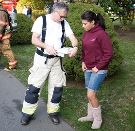 by: Chase Allgood, Kayla Varde, 14, talks to Forest Grove fire marshal Bill Bench shortly after the teen dashed inside the burning home on Birch Street to warn its residents that the house was on fire.