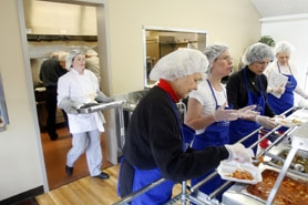 by: Jonathan House, NEW SPACE SUITS EVERYONE — Tigard Senior Center kitchen coordinator Theresa Thornton (left) carries more food out of the kitchen while a line of volunteers dishes up food Feb. 25 to be delivered for the Meals-on-Wheels program.