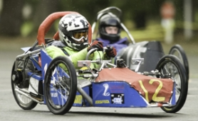 by: John Klicker, Daniel Allie of Centennial High School passes a competitor as he rounds a corner. Although electric cars travel at between 15 and 30 mph, the main objective is to complete as many laps possible in an hour's timeframe and still have battery power left.