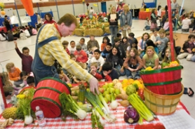 by: John Klicker, Mark Jaspers picks out a leek from a table full of fresh vegetables to pass around to grade-schoolers on Farm to Market Day at North Gresham Grade School in Gresham on Friday, March 7. Jaspers, who says he grew up on a farm in Idaho, works with Nutrition Services in the Battle Ground, Wash., school district.