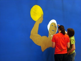 by: Jennifer Clampet, VOLUNTEERING TIME — Tualatin High seniors (from left) Maggie Alexander and Connie Rae Shobaken paint a mural of a water polo player on the gymnasium wall at Byrom Elementary School in February. The mural was part of a senior project for National Honor Society members.