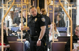by: Jonathan House, Beaverton Police Officer Ryan Potter checks for fare tickets on a MAX train at the Willow Creek/185th Avenue stop Wednesday afternoon. Potter is part of a five-person patrol that will increase security on Westside MAX trains running between the Sunset Transit Center and Hillsboro.