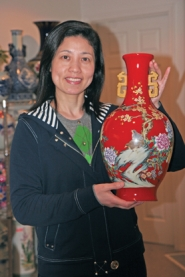 by: Gail Park, Xirong Wu shows a red vase from her collection of porcelain vases. It sits on the headboard in her guest room.