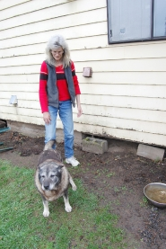 by: Darryl Swan, Linda Christophersen stands outside her Mist area home with her canine friend, Max. In December, the Nehalem River flooded, knocking support from under the home of Linda and her husband, Jack. Now the couple is having a hard time securing a fair insurance settlement.