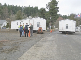 by: Submitted, A small group of onlookers watch the first FEMA delivery of manufactured homes in Vernonia on Monday. Delivery of the homes was delayed due to testing for formaldehyde levels following discovery of the known preservative in FEMA trailers in the Gulf Coast region. Testing so far has found only negligible formaldehyde levels.