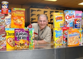 by: Patrick Sherman, Public Range Supervisor Wayne Burgin stacks up his latest haul of cereal for the Clackamas Service Center. One of these is the 1,000th box to be delivered to needy families in Clackamas.