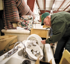 by: Chase Allgood, Harold Ortman measures a sink at ReStore, the Habitat for Humanities reclamation shop that opened on 24th Avenue in Forest Grove this month.