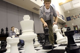 by: Jonathan House, MAKE A MOVE — Jacob Brooks makes a move on a giant chessboard during a fund-raiser for the Sherwood High School chess team at Middleton Elementary School on Monday.