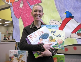 by: Barbara Sherman, BOUNTY OF BOOKS — Taking a break in front of a banner made by students to welcome her to Mary Woodward, Tigard children's author Lori Ries holds up several of her stories that have been published, including the one on the far right in Korean.