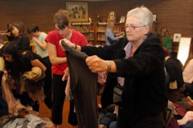 by: KATIE HARTLEY, Mary Ellen Somerville looks at a pair of pants Thursday that were brought in by another participant of the clothing swap held at the Presbyterian Church of Laurelhurst.