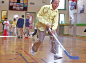 by: JIM CLARK, Fourth-grader Deaustin Clay pushes a hockey puck during PE class at Boise-Eliot, where administrators say the new dress code has brought a better attitude into the school.