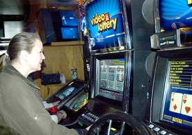 by: Rick Swart, Brenda Gamez of Portland tries her hand at one of the Oregon Lottery's video poker machines at the Wigwam Tavern in Scappoose. Video poker and line games are a $14 million a year business in Columbia County.