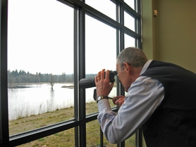 by: Kelly Moyer, A NATURAL VIEW — Bob Swanson, a volunteer at the Tualatin River National Wildlife Refuge's new Wildlife Center, peers through a telescope from the new visitors center watching a pair of bald eagles perched in a snag tree.