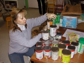 by: JIM HART, Volunteer Vickee Cosentino of West Linn checks expiration dates on canned food before weighing the donation.