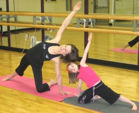 by: Kelly Moyer, REACHING OUT FOR MAMA —  Five-year-old Kaitcha Brannon (right) poses with her mother, Michelle Brannon, during a recent family yoga class at the Sherwood Regional Family YMCA. Michelle Brannon teaches family yoga classes at the YMCA on Fridays and Sundays.