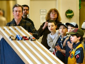 by: David F. Ashton, There are no spinning tires – but, still, plenty of excitement – as this Pine Box Derby's gatemaster, Bryan Bolster, releases the racers to run another heat.