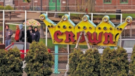 by: L.E. BASKOW, Members of the Mid-Century Modern League spent part of their St. Patrick's Day watching the Crown Motel's neon sign come down. It will go into storage for now, but members hope it will find a new home close to its old one.