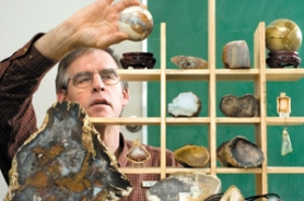 by: John Klicker, Keene Clay arranges a collection of rocks, gems and agates at his office on Monday, March 31. The collection will be on display at the Rock, Gem, and Craft Show on Saturday and Sunday, sponsored by the Mt. Hood Rock Club.