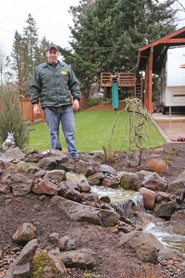 by: Gail Park, Southwest Landscape and Maintenance co-owner Don Roberts shows off the long neighbor-friendly back yard that includes a pond, a lawn, a garden, a campfire pit and a patio area.
