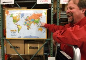 by: Jaime Valdez, ALL OVER THE MAP — Shindaiwa Inc. assembly manager Jim Parish points toward a worldwide map with red dots that designate all of the company's distributors.