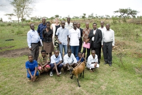 by: Submitted photo, ONE ITAFARI AT A TIME — Pictured is the first group of child-headed households in Rwanda to receive their goats. This cooperative calls themselves the Power of Love. The adults in the picture are the supporters of the program.