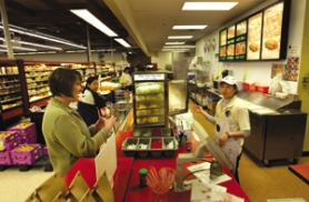 by:  L.E. BASKOW, Michelle Winningham makes a purchase from deli employee Tuanh Bui in the Fubonn Shopping Center. Winningham, a member of the citizens committee behind the East Portland Action Plan, looks forward to more community building in the area.