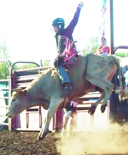 by: Linda Madsen, Austin Madsen rides a bucking bull during a recent competition