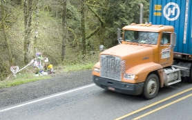 by: Rick Swart, A semi-truck barrels down Cornelius Pass Road in front of a roadside memorial to Taija Belwood, who was killed at this spot last December.