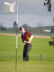 by: Chase Allgood, Forest Grove sophomore Jarek Swanson chips onto the 12th green during Monday's match at Forest Hills Golf Course.