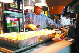 "by: Chase Allgood, Ravi Dangeti of Beaverton serves Indian snacks at Cornelius 9 Cinemas before last Saturday's screening of the Bollywood film, ""Race."""