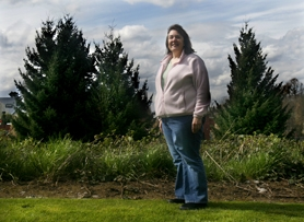 by: Jonathan House, SOME VIEW — Tualatin resident Leslie Anderson stands in her backyard where the scene of five Douglas fir trees will change drastically in the next couple months as the trees are cut down and replaced with a two-story office building.