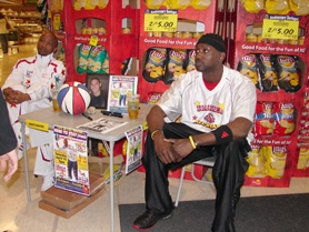 "by: Jennifer Clampet, A SLAM DUNK — Les ""Pee Wee"" Harrison sits in the Tualatin Haggen Food & Pharmacy store Saturday to drum up buzz about the Harlem Comedy All-Stars exhibition game."