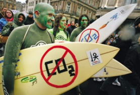 by: PETER MACDIARMID, Protesters in London take surfboards to Trafalgar Square in December to highlight climate change. In Portland, activists recently spoofed carbon offsets, which are meant to mitigate emissions of greenhouse gases.