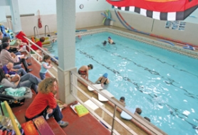 by: JIM CLARK, Parents watch as their children take part in a swimming program at the pool at the Northeast Community Center. When the YMCA announced three years ago that it would close the building, community members stepped up to save the center.
