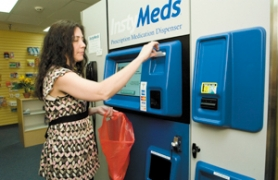 by: John Klicker, Katie Erven, a sales associate with The Shoppe at Gresham Urgent Care, takes a receipt from the InstyMeds machine Monday, April 14.