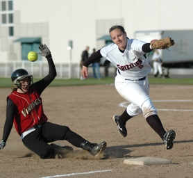 by: Zack Palmer, Forest Grove freshman Kristi Vandebergh slides into third base as the ball gets past McMinnville shortstop Alyssa Nichols.