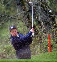 by: DAN BROOD, OUT OF THE BUNKER — Tigard senior Brad Prince hits his shot out of the bunker and on to the green on hole No. 10 during Monday's Pacific Conference tournament.