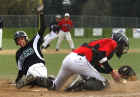 by: JONATHAN HOUSE, SAFE AT THE PLATE — Tigard High School senior Isaiah Ferrer (left) slides home safely in the bottom of the fifth inning to help the Tigers score a 5-2 win over McMinnville in Tuesday's Pacific Conference game.